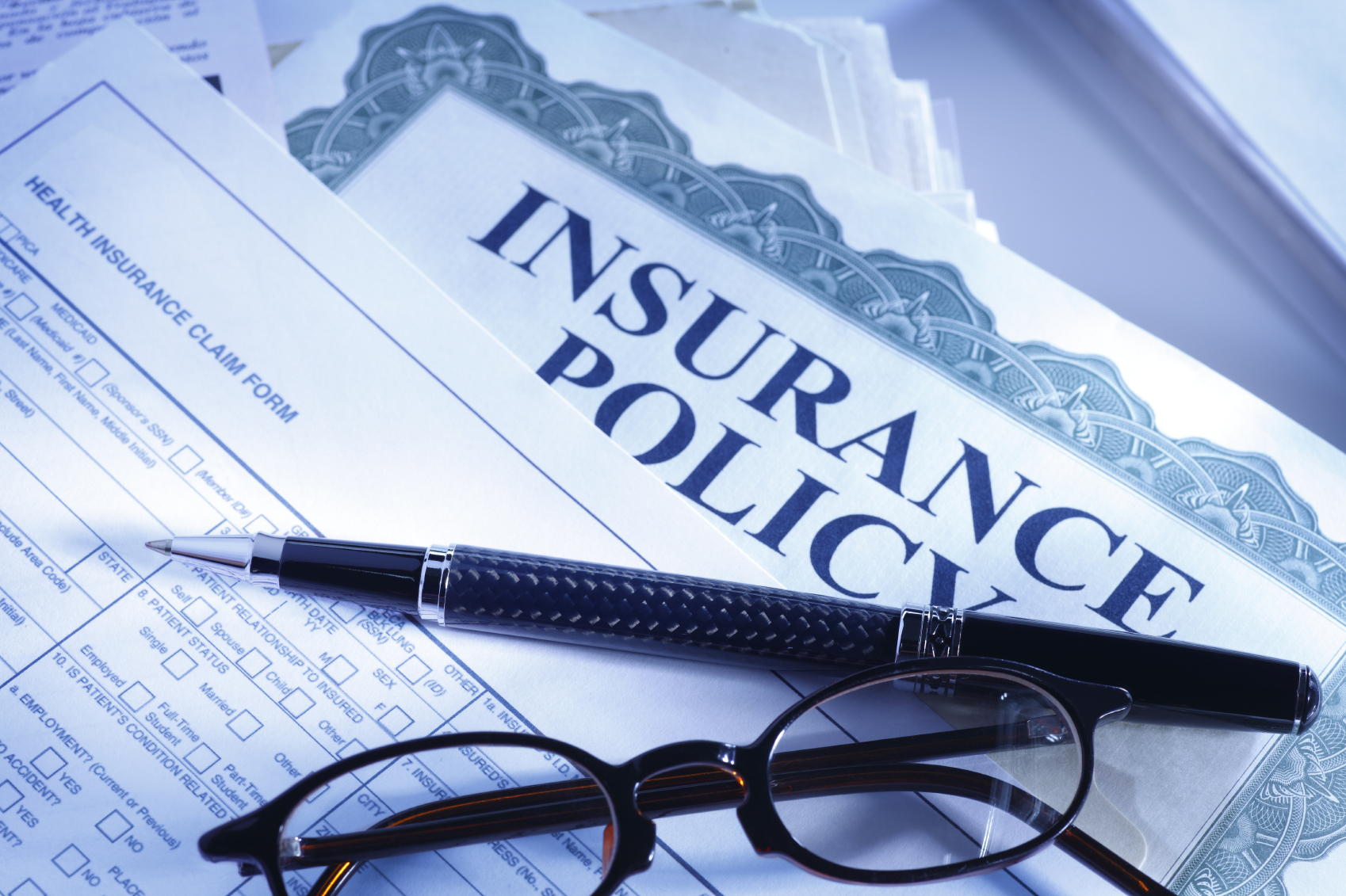 Glasses and Pen over Insurance Policy